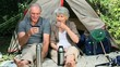 Seniors drinking coffee sitting near a tent
