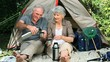 Aged couple drinking coffee sitting near a tent