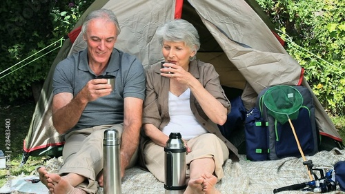 Seniors drinking coffee sitting near a tent