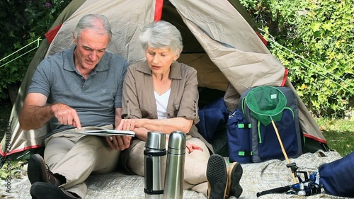 Seniors looking at a map sitting front of a tent