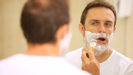Man shaving himself in front of a mirror