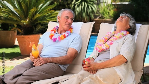 Aged couple relaxing on deckchairs