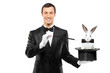 A magician in a black suit holding a top hat with a rabbit in it - 28484447