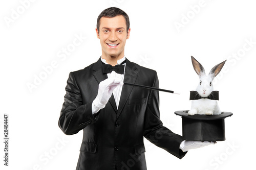 Leinwanddruck Bild A magician in a black suit holding a top hat with a rabbit in it