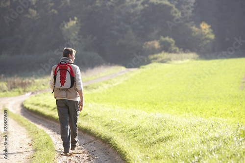 Young man walks in park