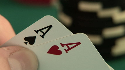 Hand holding pocket aces with poker chips