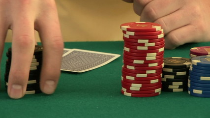 Hands betting chips while holding playing cards