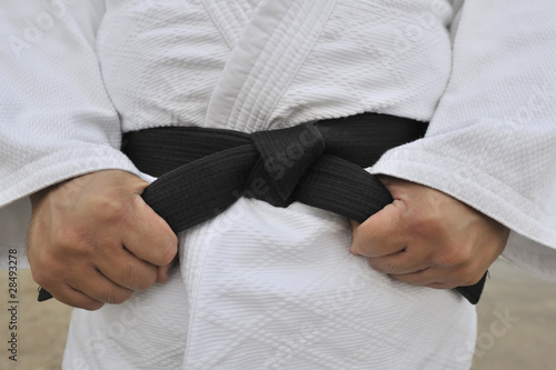 Aikido black belt knotted around waist over white uniform jacket