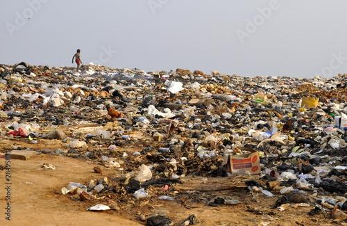 Leinwanddruck Bild Kind läuft über Müllkippe in Afrika