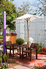Wooden furniture covered by umbrella  in garden