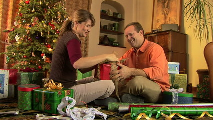 Young couple wrapping Christmas presents by the tree
