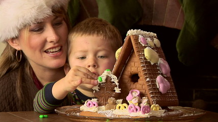 Mother and toddler son with gingerbread house at Christmas