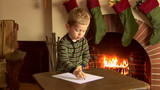 Little boy writing a letter to Santa at Christmas