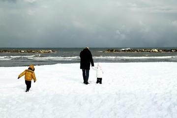 bimbi con papa' sulla spiaggia con la neve