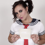 model  in a cute schoolgirl holding blank card