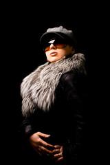 Donna con occhiali da sole e pelliccia su sfondo nero