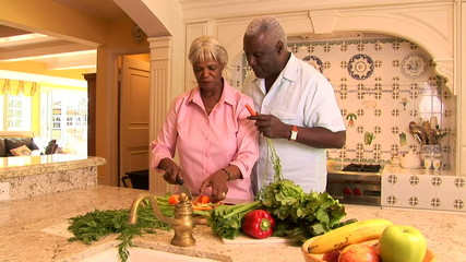 Senior couple at home in kitchen cutting fresh vegetables