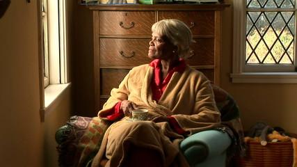 Senior woman drinking tea by bedroom window
