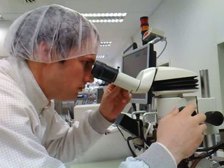 The men looks in stereomicroscope eyepieces