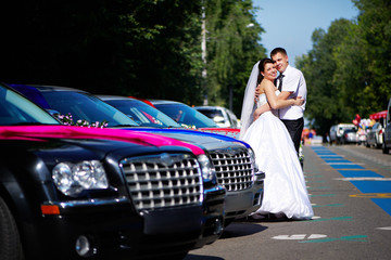 Happy bride and groom near wedding limousines