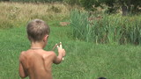 Boy shoots from a wooden slingshot summer day.