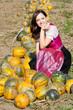 Junge Frau hinter einem Haufen von gelben Kürbissen