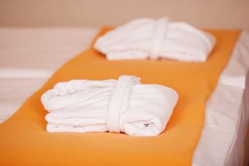 bademäntel liegen auf hotelbett