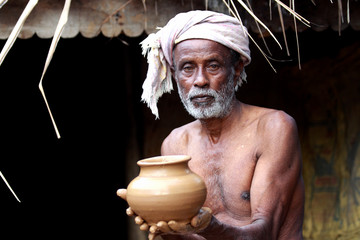 Indian Potter Showing a Pot Which He Made Just Now