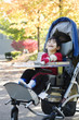 Disabled boy with cerebral palsy in medical stroller