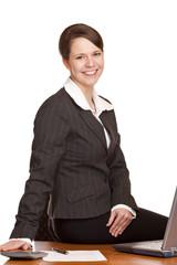 Attraktive Geschäftsfrau sitzt im Büro fröhlich auf Schreibtisch