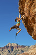 Female rock climber clinging to a cliff.