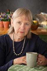 Depressed senior woman with mug
