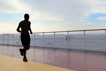 silhouette of athlete running on deck of cruised ship. evening.