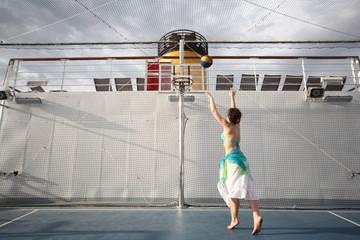 beautiful woman playing basketball on deck of cruise ship.