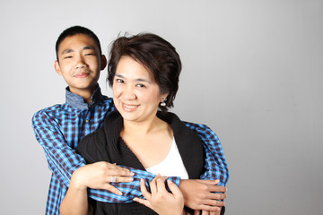 Teenage boy with funny face hugging his mother/auntie.