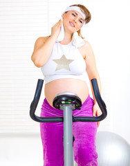 Pregnant woman wiping face with towel after training on bicycle.