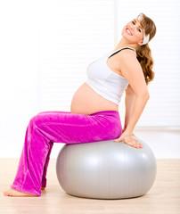 Smiling pregnant woman doing pilates exercises on gray ball.