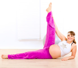Smiling beautiful pregnant woman doing exercise at home.
