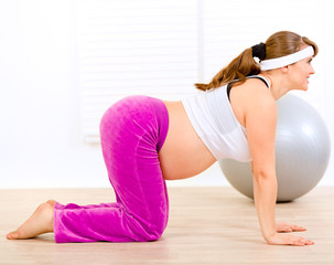 Smiling beautiful pregnant woman doing fitness exercises