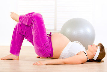 Smiling beautiful pregnant female making gymnastics at home.