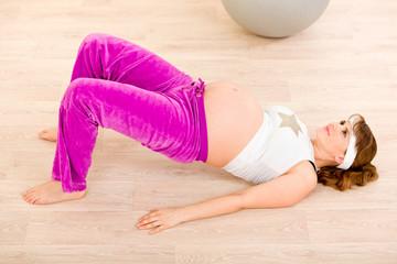 Smiling beautiful pregnant female doing fitness exercises