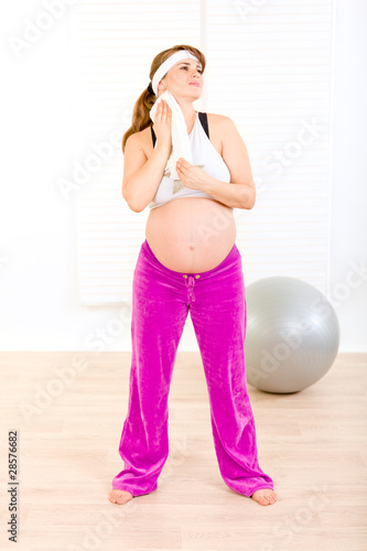 Pregnant female wiping face with towel after exercising.