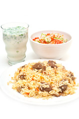Caucasian traditional pilaf, ayran and salad. Rice with meat