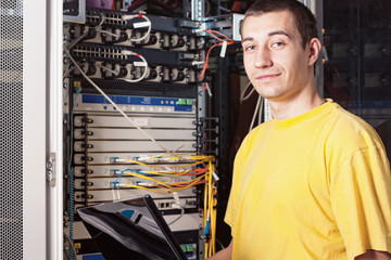 The engineer stand in datacenter near equipment
