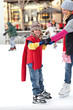 A boy hangs on to his mother while learning to ice skate.