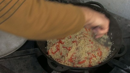Stirring pilaf with kitchen spoon, Closeup