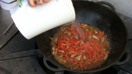 Adding hot boiled water to Pilaf ingredients in Wok, Closeup