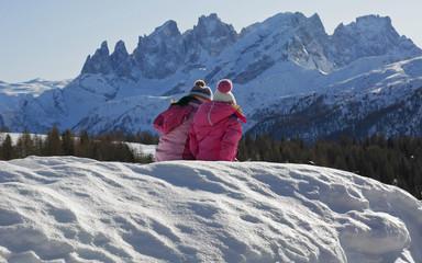 Two children are talking admiring Dolomiti landscape