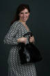 Young brunette woman with handbag. Isolated on black