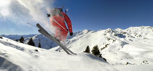 Skifahrer springt in Tiefschneehang